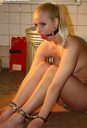 Fully nude blonde ball-gagged and restrained with a set of handcuffs..